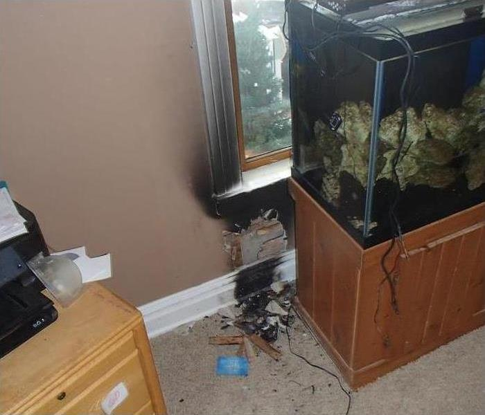 charred baseboard and window trim from small electrical fire behind the fish tank
