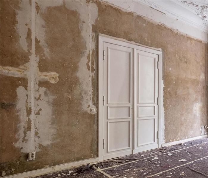 An older home with french doors and crown molding in need of restoration.