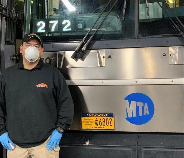 SERVPRO owner with face mask, gloves and other PPD in front of bus