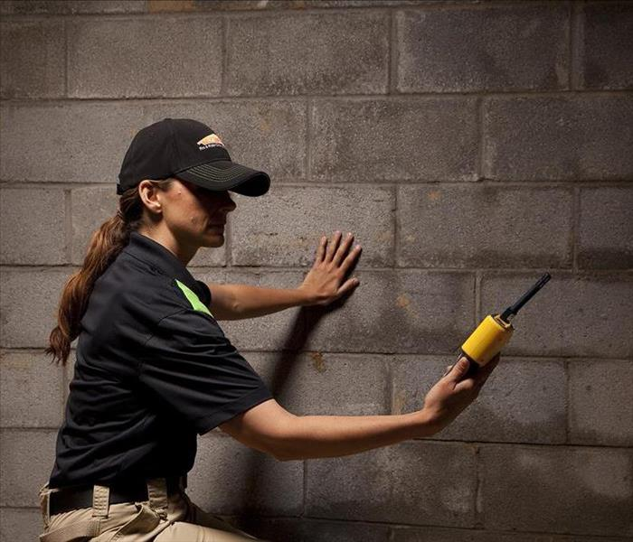 A SERVPRO technician is reading the moisture levels of this basement.